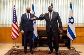 Pentagon chief Lloyd Austin, right, and Israeli Secretary of Defense Benny Ganz elbow-bump before their meeting in Jerusalem, April 11, 2021. (Twitter/@SecDef)
