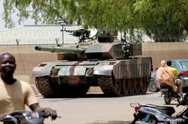 People drive past a Chad army tank near the presidential palace, as fighters from the rebel Front for Change and Concord in Chad (FACT) appeared to be moving toward the capital, according to the United States, in N'djamena, Chad, April 19, 2021.