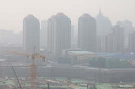 FILE - A construction site is seen against the backdrop of skyscrapers on a day with high air pollution in Beijing, China, March 11, 2021.
