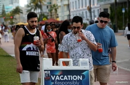 FILE - Young men read public safety precautions while enjoying the bars and restaurants on South Beach during spring break amid the coronavirus pandemic, in Miami, Florida, March 27, 2021.