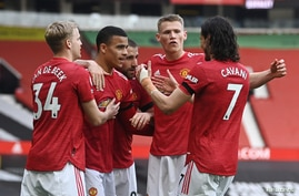 Manchester United team members celebrate scoring their second goal in their match against Burnley-Old Trafford, in Manchester, Britain, April 18, 2021.