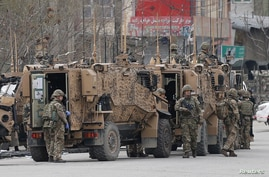 FILE - NATO soldiers inspect near the site of an attack in Kabul, Afghanistan, March 25, 2020.