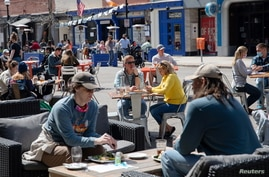 People crowd outdoor dining at a restaurant as COVID-19 restrictions are eased in Ann Arbor, Michigan, April 4, 2021.