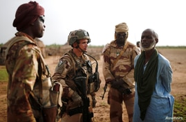 "FILE - Malian Armed Forces (FAMa) and French soldiers of the ""Belleface"" Desert Tactical Group (GTD) conduct an area control operation in the Gourma region during the Operation Barkhane in Ndaki, Mali, July 29, 2019."