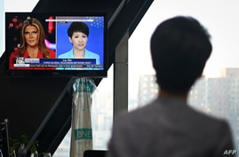 China's state broadcaster CGTN anchor Liu Xin looks at a screen showing her debate with Fox Business Network presenter Trish…