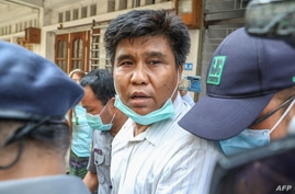 Voice of Myanmar (VOM) editor-in-chief Nay Myo Lin is escorted from his home by police to court in Mandalay on March 31, 2020. …