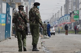 Kenyan police officers patrol in Eastleigh, Nairobi, on May 7, 2020, following the Kenyan government's announcement of partial…