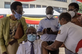 An Ugandan doctor (C-L) receives the first injection of the Oxford AstraZeneca Covid-19 vaccine at Mulago referral hospital in…