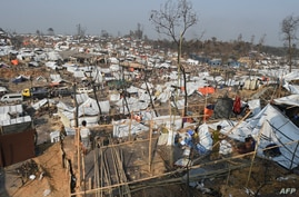 Rohingya refugee men build a temporary shelter days after a fire burnt their home at a refugee camp in Ukhia, in the…