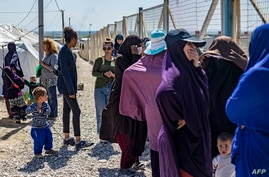 A group of women, reportedly the wives of suspected Islamic State (IS) group fighters, are pictured on March 28, 2021 at Camp…