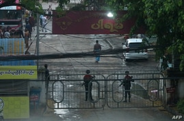 Security forces stand guard by entrance gates following an explosion at a bus station in South Okalapa township in Yangon on…
