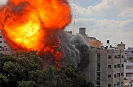 A picture taken on May 13, 2021 shows a ball of fire engulfing the Al-Walid building which was destroyed in an Israeli…