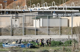 Migrants speak with Spanish Civil guards after swimming to the Spanish enclave of Ceuta from neighbouring Morocco on May 17,…