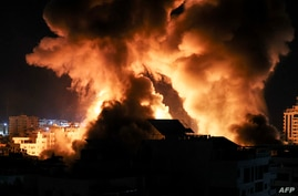 The sky is lit by an explosion above buildings in Gaza City as Israeli forces shell the Palestinian enclave, early on May 18,…