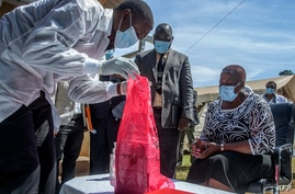 A pharmaceutical expert (L) opens a pack of expired Covid-19 Astra Zeneca vaccines to show to Malawi's Health Minister Khumbize…