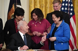 US President Joe Biden hands over a pen to Senator Mazie Hirono, D-Hawaii, after signing the Covid-19 Hate Crimes Act, in the East…