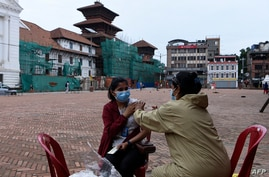A health worker inoculates a woman with the Chinese-made Vero Cell Covid-19 vaccine in Kathmandu on May 25, 2021. (Photo by…
