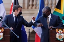 South Africa's President Cyril Ramaphosa (R) bump elbows with his French counterpart Emmanuel Macron at the end of a joint…