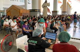 People wait to receive doses of China's Sinovac Covid-19 coronavirus vaccine at the Holy Redeemer Church in Bangkok on May 30,…