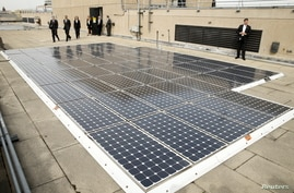 U.S. President Barack Obama is given a tour of solar panels on the roof of the Department of Energy in Washington March 19, …