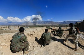 FILE - Afghan security forces take position during a gun battle between Taliban and Afghan security forces in Laghman province.