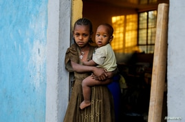 FILE PHOTO: An 11-year-old girl holds her one-year-old brother Barakat at the doorway to a classroom now used as their living…