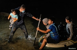 Asylum-seeking migrant families disembark from an inflatable boat after crossing the Rio Grande river into the United States.