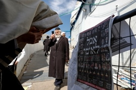"Ultra-Orthodox Jewish man reacts in front of a newspaper's front page with the Hebrew words ""National Mourning"", at the site…"