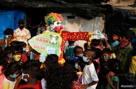 A man dressed as a clown distributes face masks to children in a slum area, amidst the coronavirus disease (COVID-19) outbreak,…