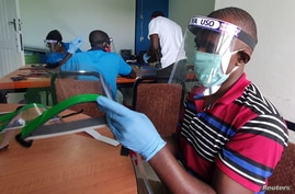FILE PHOTO: Workers prepare face shields from recycled plastics at the Zaidi Recyclers workshop as a measure to stop the spread…