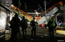 Soldiers stand as rescuers work at a site where an overpass for a metro partially collapsed with train cars on it.