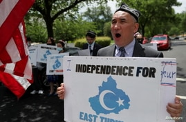 Demonstrators, including Aziz Sulayman, hold a protest in front of the U.S. State Department to commemorate Uyghur Doppa Day…