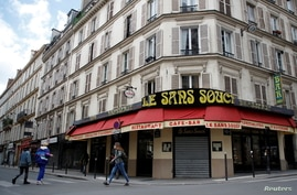 FILE - People walk past a closed restaurant in Paris amid the coronavirus disease (COVID-19) outbreak in France.