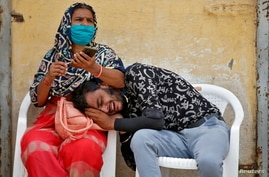 A man mourns after his father died due to the coronavirus disease (COVID-19) outside a mortuary in Ahmedabad, India.