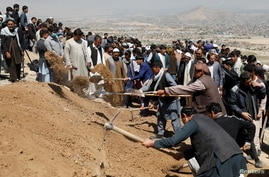 Men dig graves for the victims of yesterday's explosion during a mass funeral ceremony in Kabul, Afghanistan May 9, 2021…