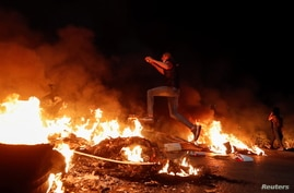 A Palestinian demonstrator jumps over a burning barricade during an anti-Israel protest over tension in Jerusalem.