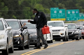 A friend carrying a gas container is greeted by a motorist waiting in a lengthy line to enter a gasoline station during a surge…