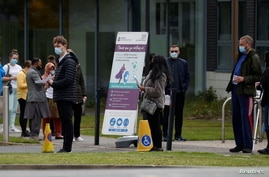 People line up outside a mobile vaccination centre, amid the outbreak of the coronavirus disease (COVID-19), in Bolton, Britain…