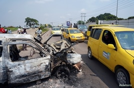 A taxi passenger looks at a burned police car, after two groups of Muslims clashed outside Martyrs Stadium in Kinshasa,…