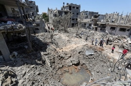 Palestinians gather at the site of destroyed houses in the aftermath of Israeli air and artillery strikes as cross-border…