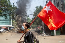 FILE - A man holds a National League for Democracy (NLD) flag during a protest against the military coup, in Yangon, Myanmar March 27, 2021.