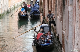 Tourists enjoy a gondola ride as Italy lifts quarantine restrictions for travellers arriving from European Union countries,…