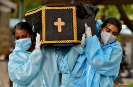 Volunteers, Akshaya (R), 22, a law student, and Esther Mary, 41, a lecturer, carry the body of a person who died from COVID.