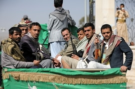 FILE PHOTO: Armed Houthi followers ride on the back of a truck after participating in a funeral of Houthi fighters killed in…