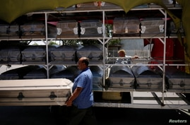 Vendors carry a coffin to deliver it to a funeral home as the coronavirus disease (COVID-19) outbreak continues, in Ciudad…