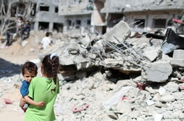 A Palestinian girl carries a boy amid the rubble of their houses which were destroyed by Israeli air strikes during the Israel…