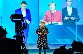 Norway's Prime Minister Erna Solberg and German Chancellor Angela Merkel (on screen) participate in the official opening of…