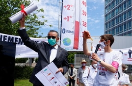 World Health Organization (WHO) Director General Tedros Adhanom Ghebreyesus holds a letter which was presented to him by a member of Doctors for XR (Extinction Rebellion) urging him to take action on climate change, in Geneva, Switzerland, May 29, 2021.