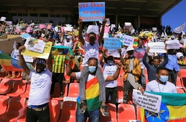Ethiopian pro-government demonstrators carry placards as they attend a rally to protest against the U.S. action over alleged…