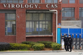 Security personnel gather near the entrance of the Wuhan Institute of Virology during a visit by the World Health Organization…
